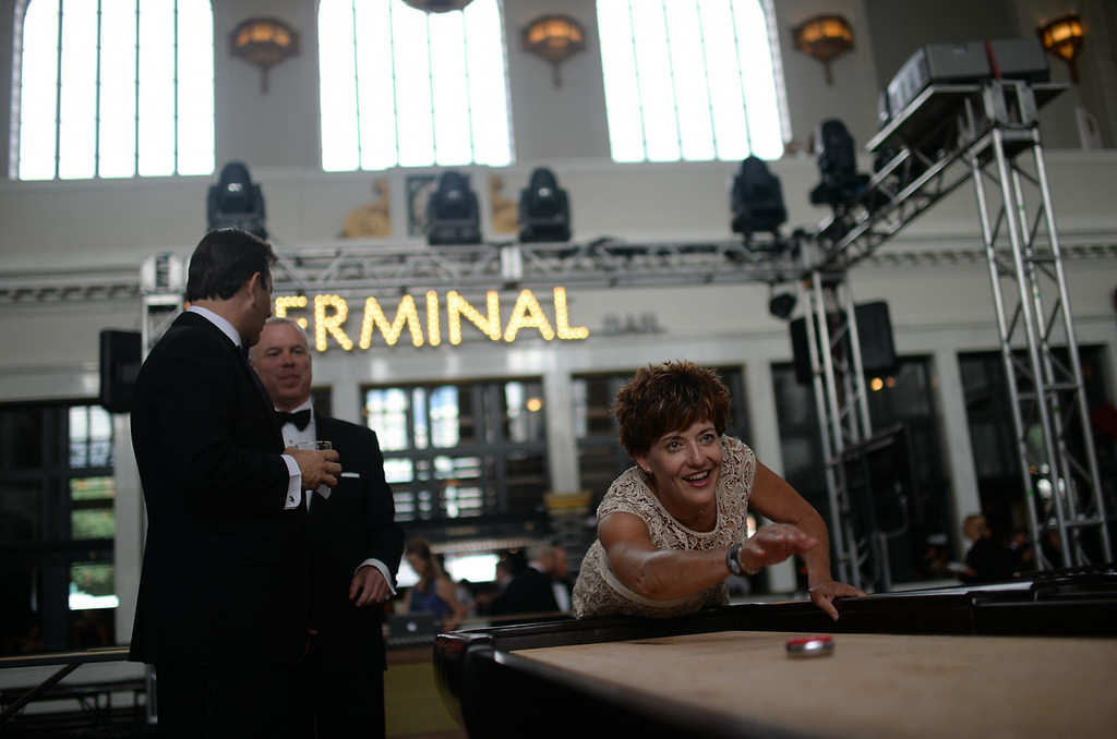 . DENVER, CO - JULY 11: Kelly Brough of Denver Metro Chamber of Commerce, right, is playing shuffleboard during Denver Union Station Great Hall Gala in Denver, Colorado July 11, 2014. Union Station is opening with the gala for 1,000 people paying $1,000 each to benefit 55 local charities.(Photo by Hyoung Chang/The Denver Post)