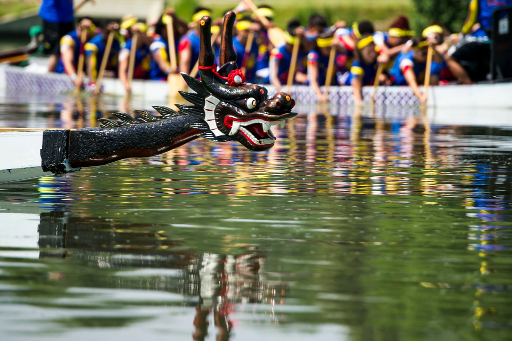 . A Dragon Boat is seen returning to shore with The Philippine-American Society of Colorado Fighting Dragons in the background during the 2014 Colorado Dragon Boat Festival at Sloan\'s Lake Park on Sunday, July 20, 2014 in Denver, CO.  The event featured 100 performances on 5 stages, 21 food vendors in two food Taste of Asia courts, more than 40 Marketplace Exhibitors, and the exciting ancient sport of Dragon Boat Racing.  (Photo by Kent Nishimura/The Denver Post)