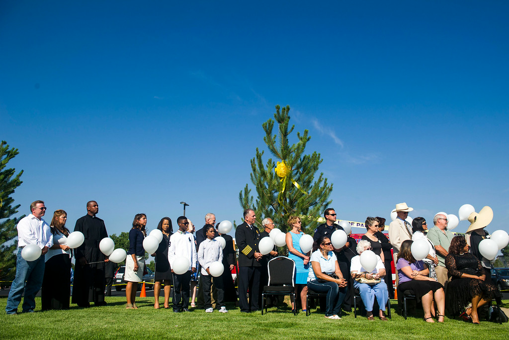 . Family and friends of the 12 people who lost their lives in the Aurora Theater shooting of 2012, and members of The Potter\'s House ministries are seen standing in front of a tree during a dedication ceremony for the newly planted trees at Hope Park at The Potter\'s House of Denver on Sunday, July 20, 2014 in Aurora, CO.  Each tree planted bore a yellow ribbon with the name of a person who lost their life in the tragedy.  (Photo by Kent Nishimura/The Denver Post)