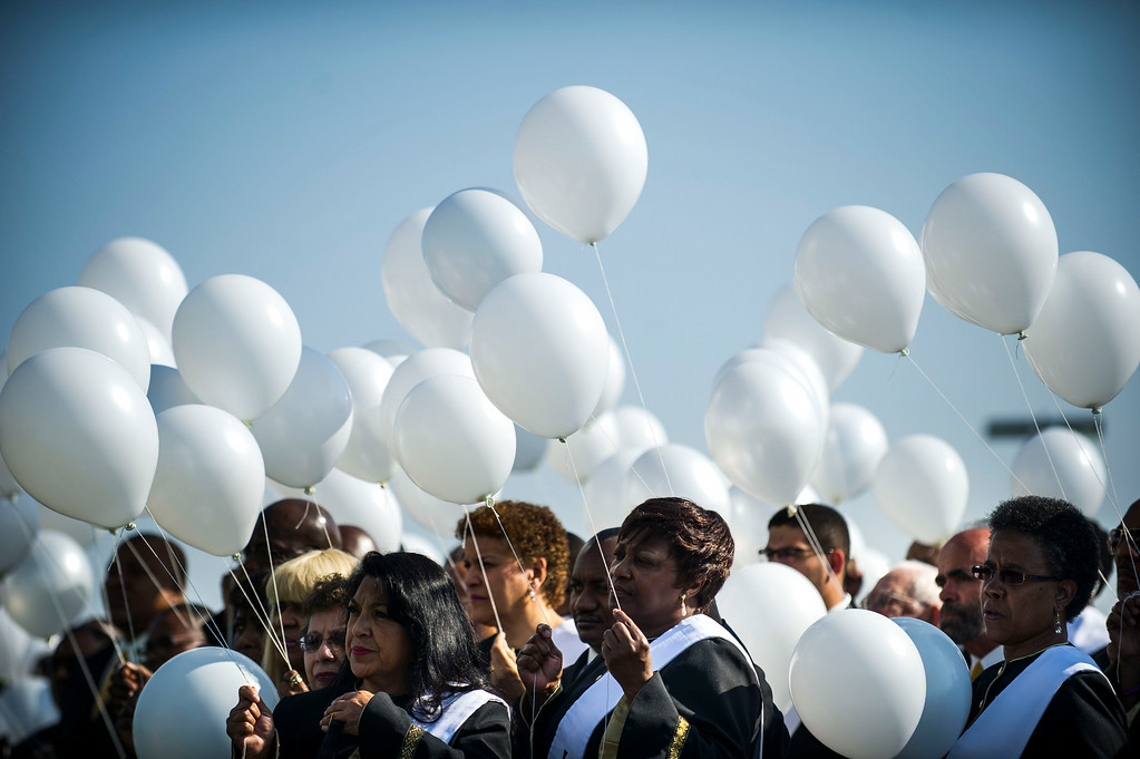 . People hold white balloons during a dedication ceremony for the newly planted trees at Hope Park at The Potter\'s House of Denver on Sunday, July 20, 2014 in Aurora, CO.  Each tree planted bore a yellow ribbon with the name of a person who lost their life in the tragedy.  (Photo by Kent Nishimura/The Denver Post)