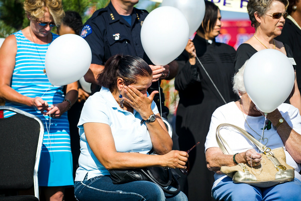 . Gloria Rodriguez wipes away tears during a dedication ceremony for the newly planted trees at Hope Park at The Potter\'s House of Denver on Sunday, July 20, 2014 in Aurora, CO.  Each tree planted bore a yellow ribbon with the name of a person who lost their life in the tragedy.  (Photo by Kent Nishimura/The Denver Post)