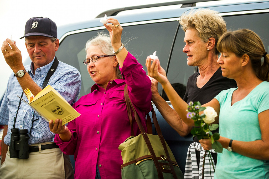 . Volunteers Tom Kelly, Karen Tonso, Linda Chambers, and Dorothy Gibson raise candles as Karen reads a passage from The Prophet in honor the eaglet that the Raptor Education Foundation had been observing at an eagle\'s nest along E120th Avenue near, E-470 on Sunday, July 27, 2014 in Commerce City, Colorado.  (Photo by Kent Nishimura/The Denver Post)