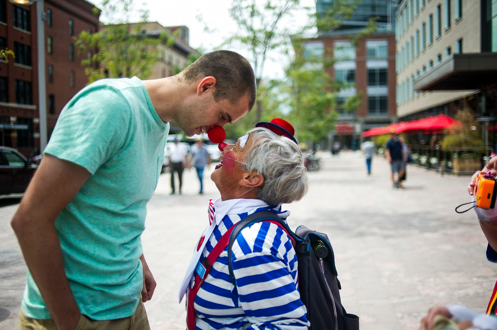 . DENVER, CO - AUGUST 04:  Scott Guberud bumps noses with Fran Etzkorn, Kolo the clown, along Wynkoop Street in front of Union Station on Monday, August 04, 2014 in Denver, Colorado.   The members of the Colorado Clown Alley were out at Union Station and the 16th Street Mall in celebration of International Clown Week which runs from August 1-7.  (Photo by Kent Nishimura/The Denver Post)