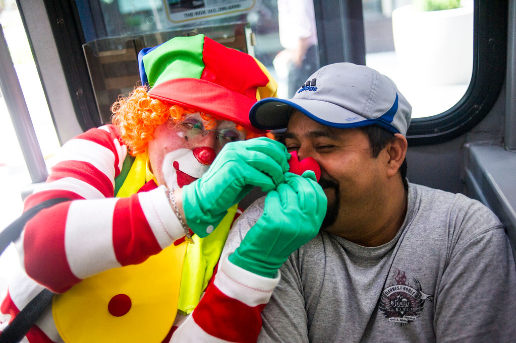 . DENVER, CO - AUGUST 04:  Lynn Imig, Sprinkles the Clown, puts a clown nose on a man who only gave his name Jose while riding the 16th Street Mall Ride on Monday, August 04, 2014 in Denver, Colorado.  The members of the Colorado Clown Alley were out at Union Station and the 16th Street Mall in celebration of International Clown Week which runs from August 1-7.  (Photo by Kent Nishimura/The Denver Post)
