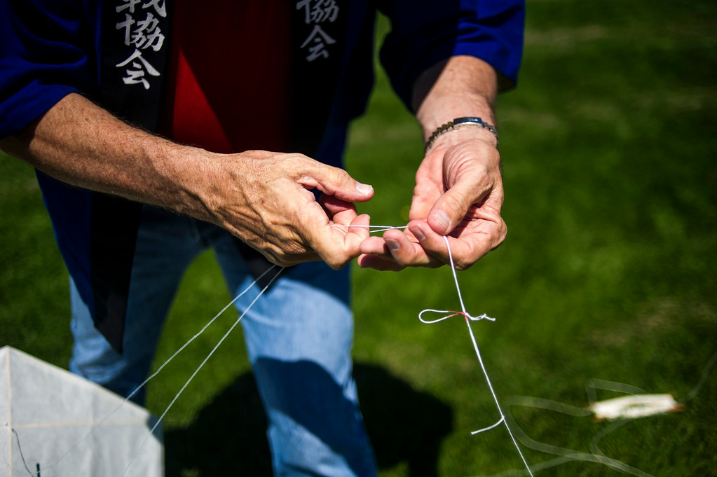 . DENVER, CO - AUGUST 06:  Scott Skinner adjusts the bridle line of a kite during the Japanese Kite Festival at the Pavilion at Stapleton Central Park on Wednesday, August 06, 2014 in Denver, Colorado.  The event featured a demonstration by Japanese Kite Master Mikio Toki of Japan and a chance to make your own kites.  (Photo by Kent Nishimura/The Denver Post)