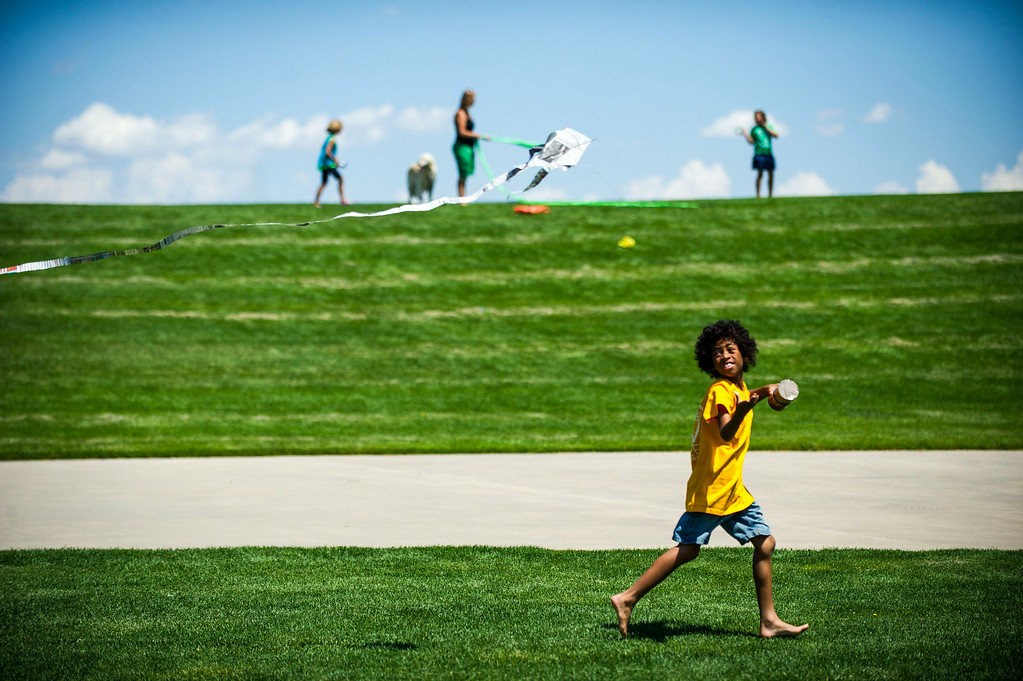 . DENVER, Colorado - AUGUST 06:  Amir Belen, 9, runs with a kite his father made during the Japanese Kite Festival at the Pavilion at Stapleton Central Park on Wednesday, August 06, 2014 in Denver, Colorado.  The event featured a demonstration by Japanese Kite Master Mikio Toki of Japan and a chance to make your own kites.  (Photo by Kent Nishimura/The Denver Post)