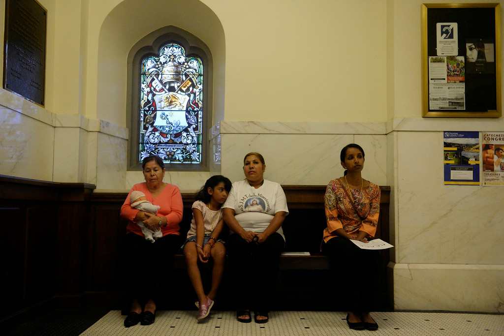 . From left to right: Rosala Saenz, Bethany Velasquez, 8, Martha Saenz and Teema Cyriac listen as various religious leaders lead a group of people in prayer and peace during an inter-faith gathering. The Place Initiative: Peace, Love and Co-Existence, an inter-faith assembly, was photographed on Monday, August 11, 2014. (Photo by AAron Ontiveroz/The Denver Post)
