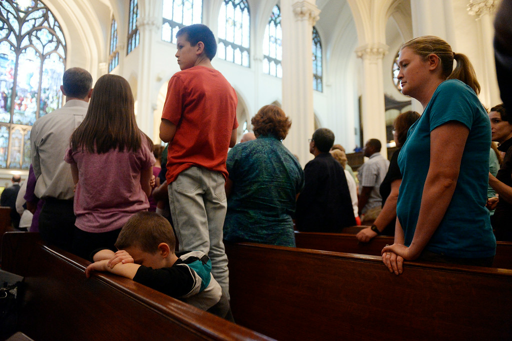 . Brian Beckman, 7, bows his head on the pew as his brother, Jonathan, 11, stands on the pew for a better view as various religious leaders lead the congregation in prayer. The Place Initiative: Peace, Love and Co-Existence, an inter-faith assembly, was photographed on Monday, August 11, 2014. (Photo by AAron Ontiveroz/The Denver Post)