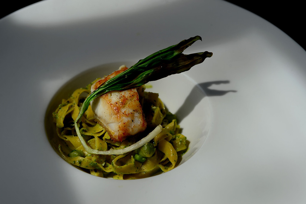 . This is an entree of fresh grouper from the Gulf of Mexico with tagliatelle pasta with pesto and fresh garbanzo beans and ramps on top prepared by Chef Andrea Frizzi, of Il Posto restaurant  in Denver on April 17, 2014.The fresh fish had just come out of the box that had just been delivered from Seattle Fish Company at his restaurant in Denver, Co on April 17, 2014.  (Photo By Helen H. Richardson/ The Denver Post)
