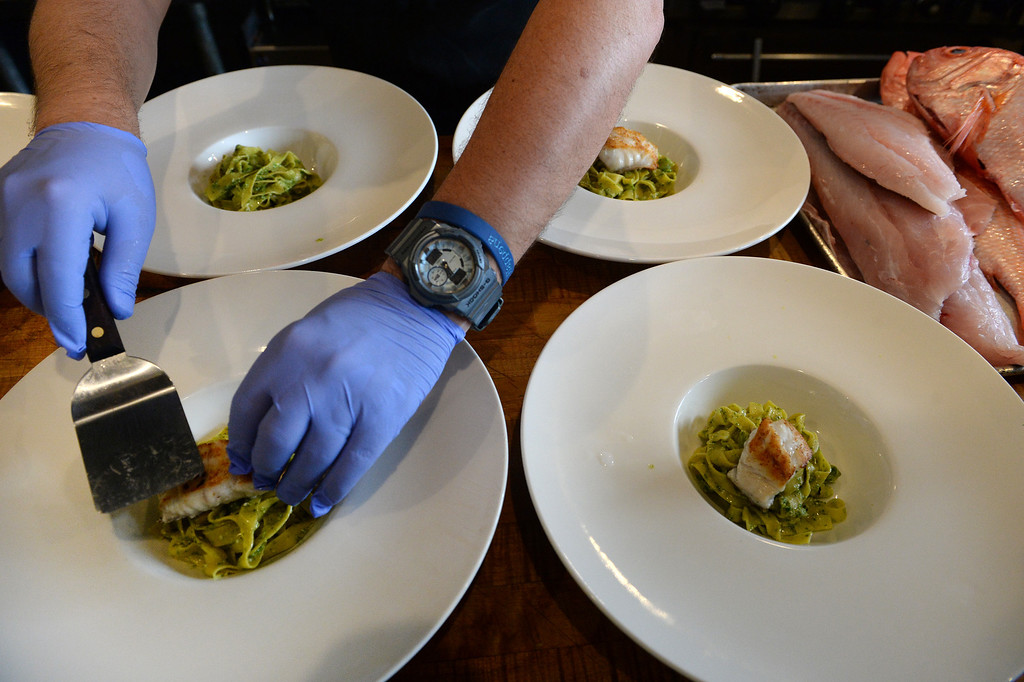 . Chef Andrea Frizzi, of Il Posto restaurant, prepares a pasta dish of tagliatelle pasta with pesto, ramps, fresh garbanzo beans and fresh grouper from the Gulf of Mexico in Denver on April 17, 2014.The fish at right is  fresh red snapper from New Zealand on the right and grouper, in the middle, that had just come out of the box that had just been delivered from Seattle Fish Company at his restaurant in Denver, Co on April 17, 2014.  (Photo By Helen H. Richardson/ The Denver Post)