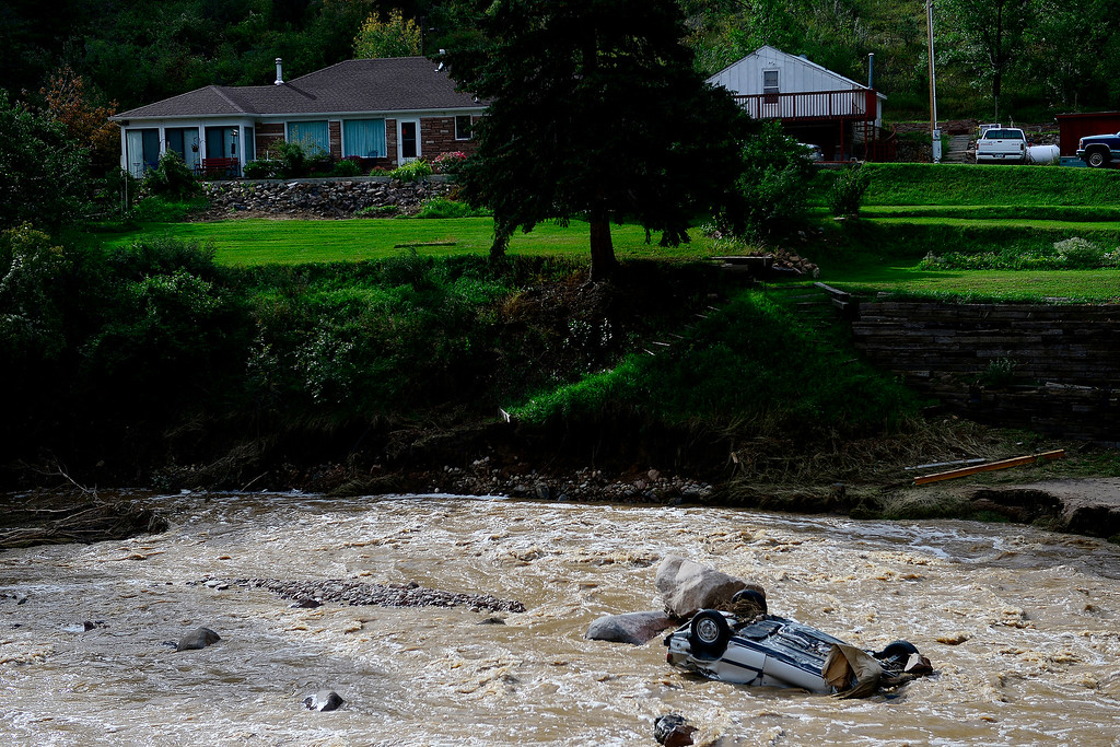 . A car lies upside down in front of a property during a tour to look at the damage caused by recent flooding in the area on U.S. Highway 36 between Lyons and Pinewood Springs. Pavement is missing in many section of the road that connects Lyons to Estes Park. (Photo by AAron Ontiveroz/The Denver Post)