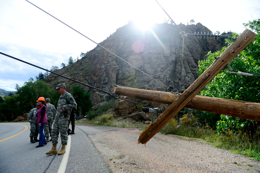 . Colorado National Guard soldiers lead a group of CDOT and state employees near a downed pole during a tour to look at the damage caused by recent flooding in the area on U.S. Highway 36 between Lyons and Pinewood Springs. Pavement is missing in many section of the road that connects Lyons to Estes Park. (Photo by AAron Ontiveroz/The Denver Post)