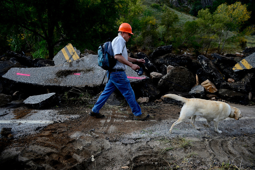 . CDOT executive director Don Hunt walks the road with his dog Sasha during a tour to look at the damage caused by recent flooding in the area on U.S. Highway 36 between Lyons and Pinewood Springs. Pavement is missing in many section of the road that connects Lyons to Estes Park. (Photo by AAron Ontiveroz/The Denver Post)