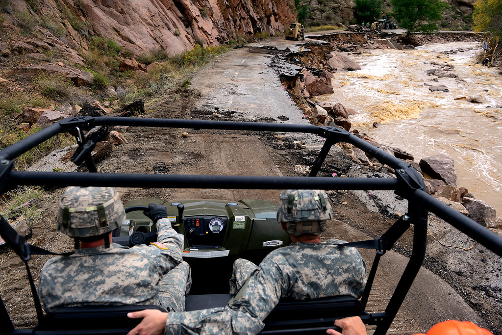 . Colorado National guardsman David Yows drives with fellow gurdsman Christopher Cole during a tour to look at the damage caused by recent flooding in the area on U.S. Highway 36 between Lyons and Pinewood Springs. Workers are attempting to have some access to the road by December 1. (Photo by AAron Ontiveroz/The Denver Post)