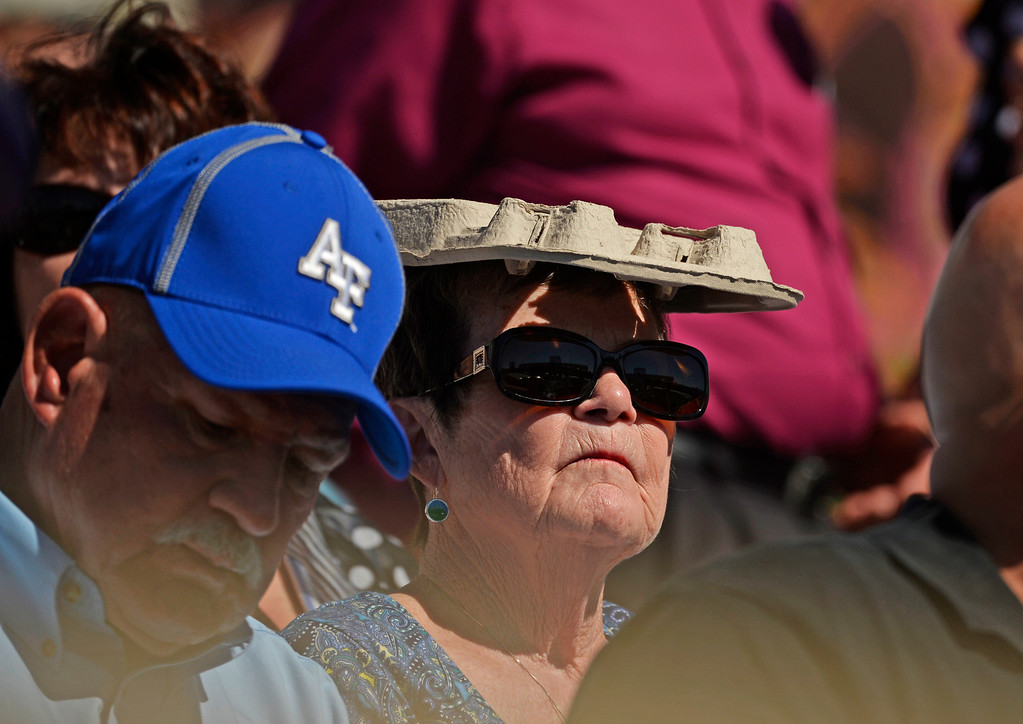 . A women in the crowd, during the commencement ceremony at Air Force Academy in Colorado Spring, uses a drinks tray to keep out of the sun, May 28, 2014.  (Photo by RJ Sangosti/The Denver Post)