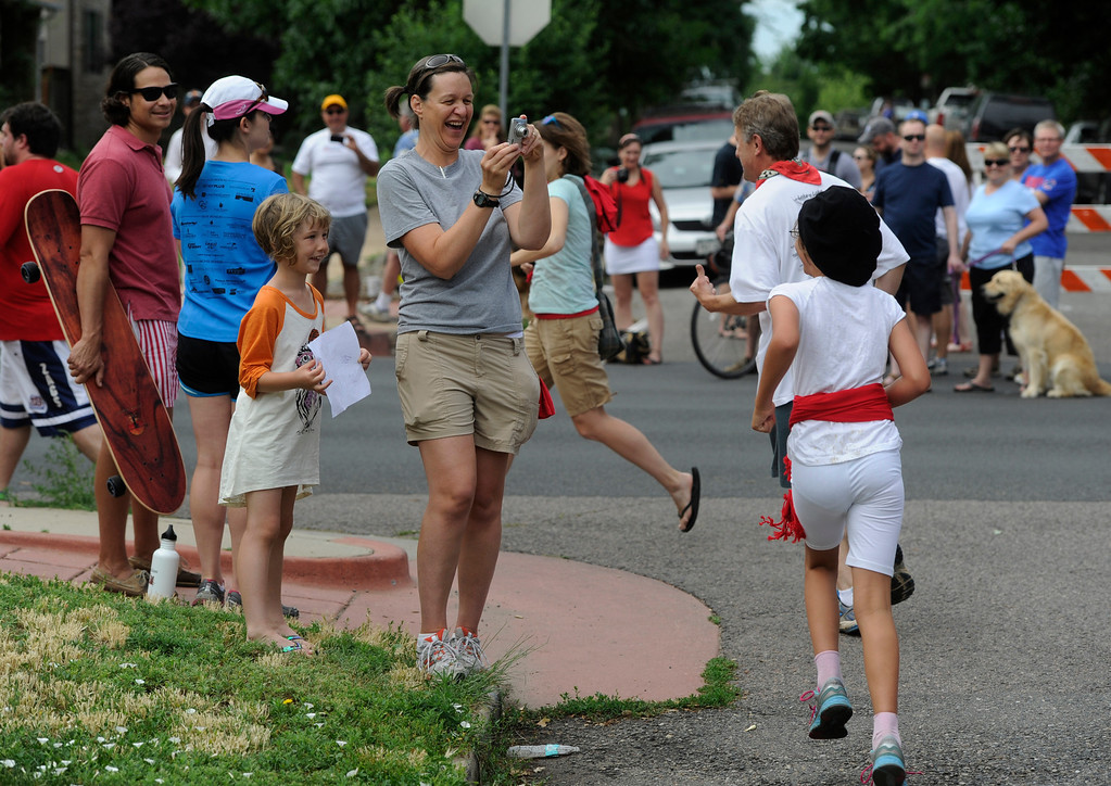 . DENVER, CO - JULY 13: Spectators line Raleigh St. at 32nd Ave during the third annual Highland Running of the Bulls one-mile race in the Highland neighborhood in Denver Colorado Saturday morning, July 13, 2013. Inspired by the running of the bulls in Pamplona Spain, runners get chased through the course by the Rocky Mountain Rollergirls wielding foam and plastic bats, proceeds from the race benefit the Tennyson Center for Children whose aim is to �work with children, youth, and their families to overcome a variety of life crises, including abuse and neglect.� (Photo By Andy Cross/The Denver Post)