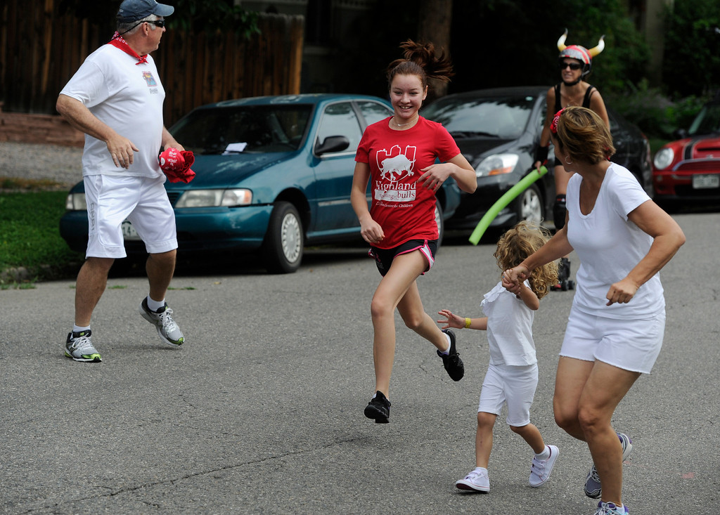 . DENVER, CO - JULY 13: Runners try to avoid getting whacked with a piece of foam from an approaching Rocky Mountain Rollergirl during the third annual Highland Running of the Bulls one-mile race in the Highland neighborhood in Denver Colorado Saturday morning, July 13, 2013. Inspired by the running of the bulls in Pamplona Spain, runners get chased through the course by the Rocky Mountain Rollergirls wielding foam and plastic bats, proceeds from the race benefit the Tennyson Center for Children whose aim is to �work with children, youth, and their families to overcome a variety of life crises, including abuse and neglect.� (Photo By Andy Cross/The Denver Post)