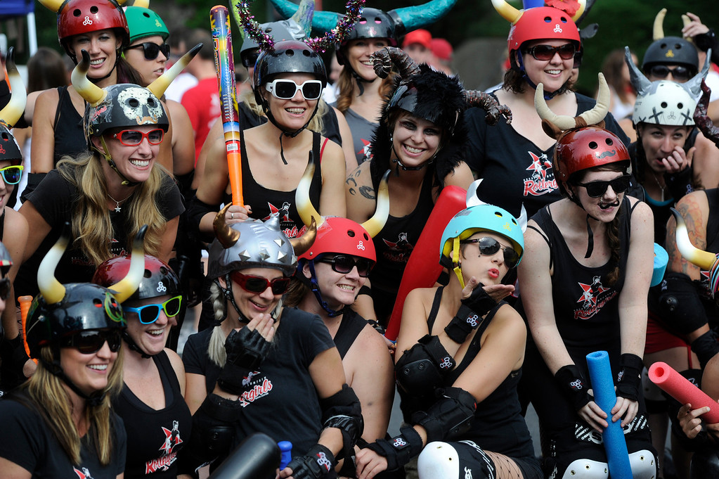 . DENVER, CO - JULY 13: The Rocky Mountain Rollergirls pose for group pictures at the start line of the third annual Highland Running of the Bulls one-mile race in the Highland neighborhood in Denver Colorado Saturday morning, July 13, 2013. Inspired by the running of the bulls in Pamplona Spain, runners get chased through the course by the Rocky Mountain Rollergirls wielding foam and plastic bats, proceeds from the race benefit the Tennyson Center for Children whose aim is to �work with children, youth, and their families to overcome a variety of life crises, including abuse and neglect.� (Photo By Andy Cross/The Denver Post)