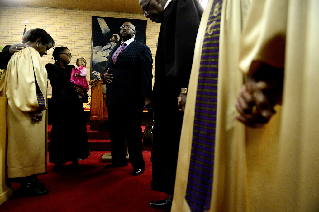 . Pastor Victor-LaMonte Lane, standing next to his wife, Taihesaia, who is holding their daughter, Abigail, as he leads the choir in prayer at Macedonia Baptist church in Denver on November 24, 2013. Lane was officially installed as the new pastor of the church on December 6, 2013. (Photo by AAron Ontiveroz/The Denver Post)