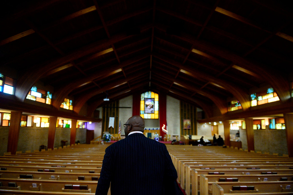 . Pastor Victor-LaMonte Lane walks into the sanctuary before a Sunday service at Macedonia Baptist church in Denver on November 24, 2013. Lane was officially installed as the new pastor of Macedonia Baptist church on December 6, 2013. (Photo by AAron Ontiveroz/The Denver Post)
