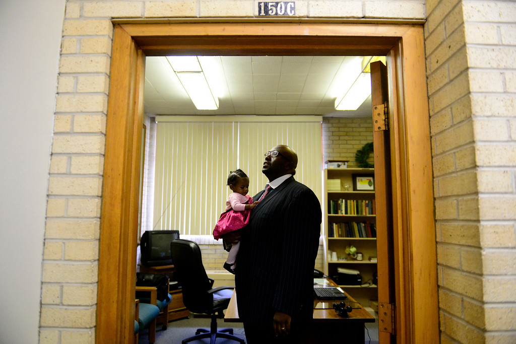 . Pastor Victor-LaMonte Lane holds his daughter Abigail in his new office before the Sunday service at Macedonia Baptist church in Denver on November 24, 2013. Lane was officially installed as the new pastor of Macedonia Baptist church on December 6, 2013. (Photo by AAron Ontiveroz/The Denver Post)