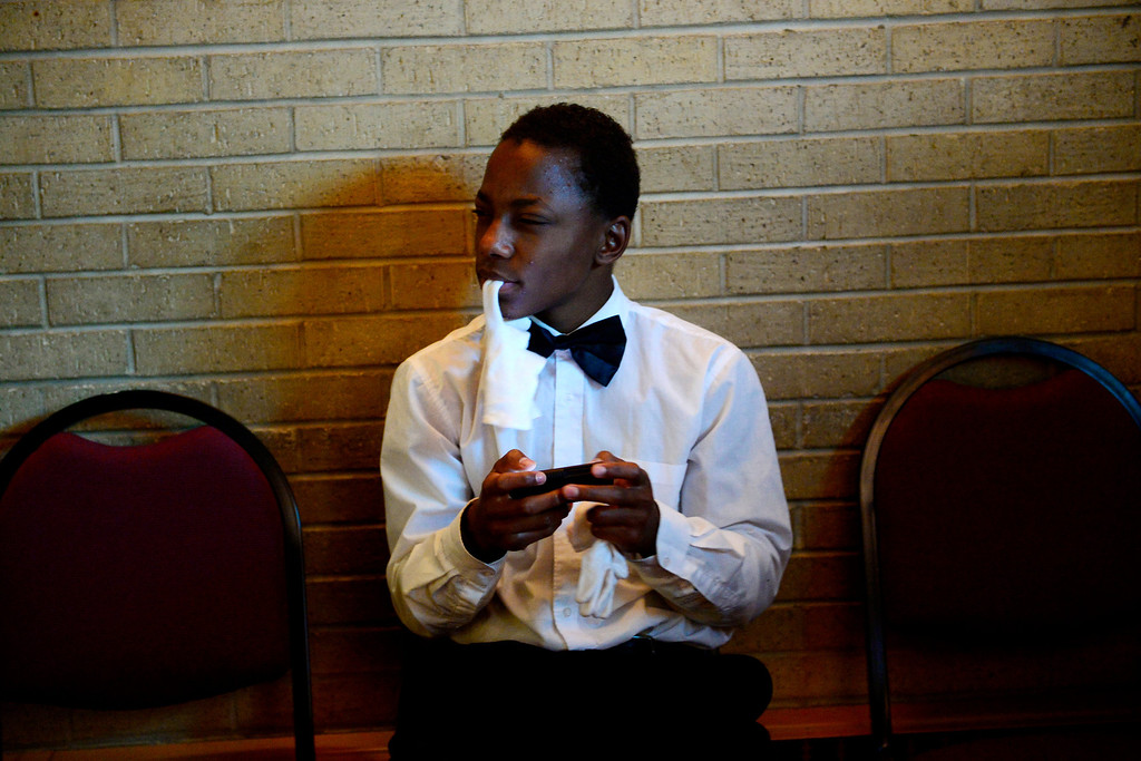 . Darerl Burton, 15, holds his white usher\'s glove while he uses his phone at Macedonia Baptist church in Denver on November 24, 2013. (Photo by AAron Ontiveroz/The Denver Post)