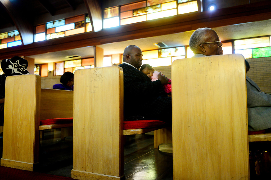 . Pastor Victor-LaMonte Lane prays along with fellow parishioners while holding his daughter Abigail at Macedonia Baptist church in Denver on November 24, 2013. Lane was installed as the new pastor of Macedonia Baptist church on December 6, 2013. (Photo by AAron Ontiveroz/The Denver Post)