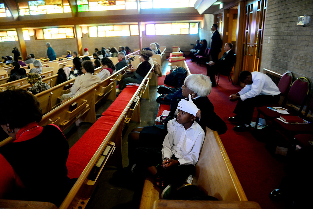 . Gloria Smith holds the head of Xavier Kimbrough, 8, as they listen to the sermon at Macedonia Baptist church in Denver on November 24, 2013. Pastor Victor-LaMonte Lane was installed as the new pastor of the church on December 6, 2013. (Photo by AAron Ontiveroz/The Denver Post)