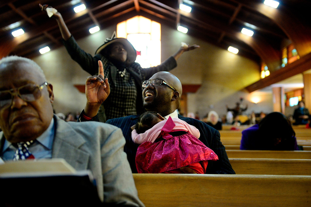 . Pastor Victor-LaMonte Lane sings along with fellow parishioners while holding his daughter Abigail at Macedonia Baptist church in Denver on November 24, 2013. Lane was officially installed as the new pastor of the church on December 6, 2013. (Photo by AAron Ontiveroz/The Denver Post)