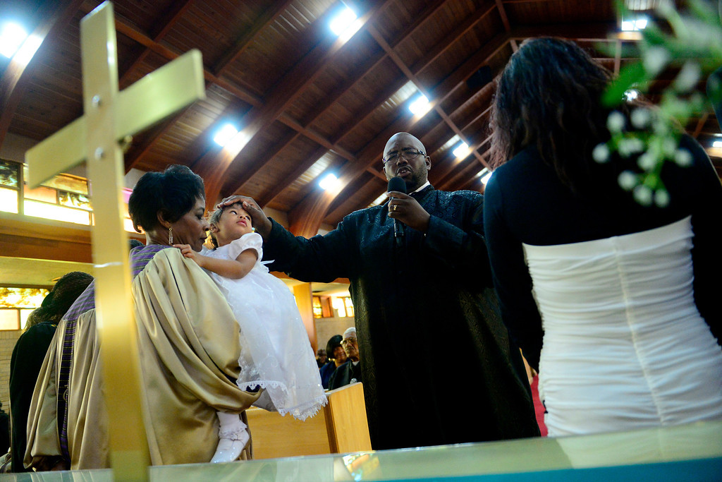 . Pastor Victor-LaMonte Lane performs a blessing on Tatyianna Skyy Parrish during the Sunday service at Macedonia Baptist in Denver church on November 24, 2013. Lane was officially installed as the new pastor of the church on December 6, 2013. (Photo by AAron Ontiveroz/The Denver Post)