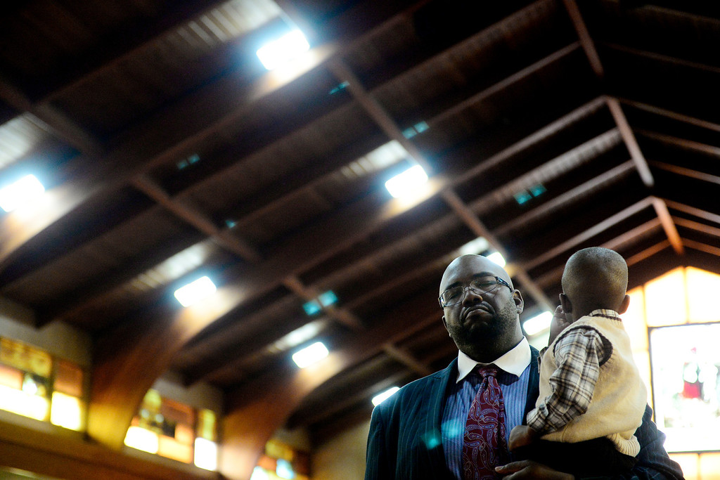 . Pastor Victor-LaMonte Lane holds his son Josiah, 2, during Sunday\'s service at Macedonia Baptist church in Denver on November 24, 2013. Lane was officially installed as the new pastor of Macedonia Baptist church on December 6, 2013. (Photo by AAron Ontiveroz/The Denver Post)