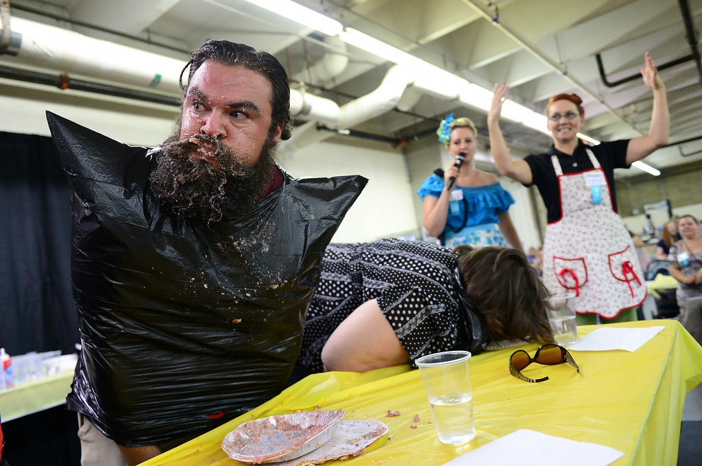 . Dan Baker looks to see if he is the first to finish his pie, as Marnie Ward, right, and Michelle Baldwin, second from right, encourage the pie eating contestants to finish, during the homemade pie eating contest at the Denver County Fair at the National Western Complex in Denver, CO on August 3rd, 2014. Baker won the contest.  This was the last day of the fair which included dancing, singing, dog agility courses, freak shows, and pie eating contests. (Photo by Helen H. Richardson/The Denver Post)