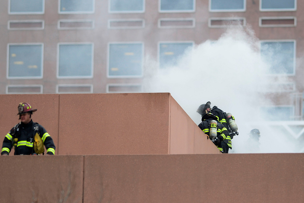 . Fire crews work to put out a fire at a parking garage on 17th and Grant. A mechanical room began to burn and fire crews quickly put it out. As a precaution, the adjacent building was evacuated. (Photo by AAron Ontiveroz/The Denver Post)