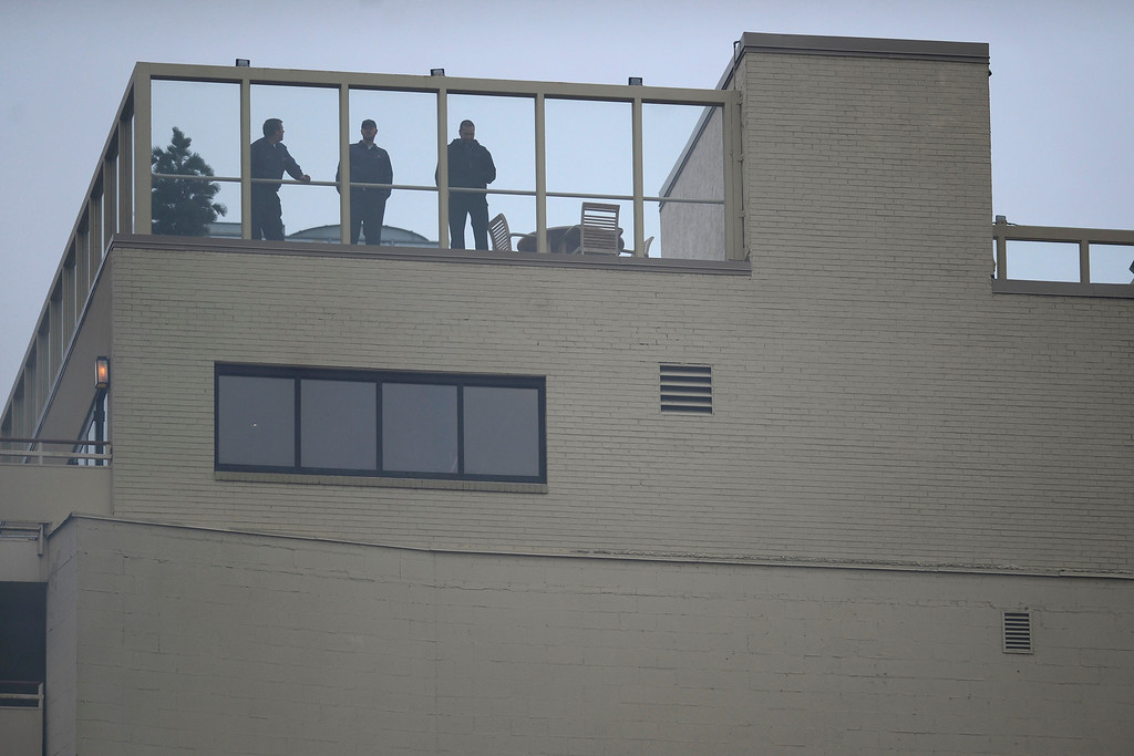 . People watch from the roof of Warwick\'s Hotel as fire crews work to put out a fire at a parking garage on 17th and Grant. A mechanical room began to burn and fire crews quickly put it out. As a precaution, the adjacent building was evacuated. (Photo by AAron Ontiveroz/The Denver Post)