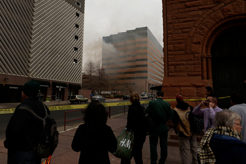 . People watch from the street as fire crews work to put out a fire at a parking garage on 17th and Grant. A mechanical room began to burn and fire crews quickly put it out. As a precaution, the adjacent building was evacuated. (Photo by RJ Sangosti/The Denver Post)