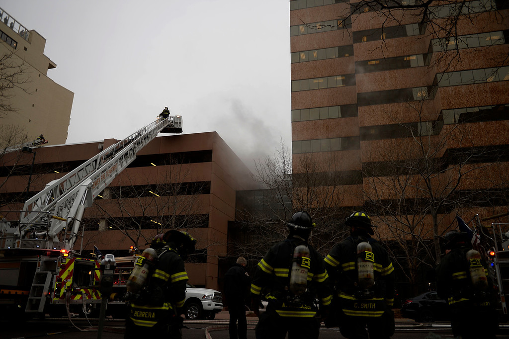 . Fire crews work to put out a fire at a parking garage on 17th and Grant. A mechanical room began to burn and fire crews quickly put it out. As a precaution, the adjacent building was evacuated. (Photo by RJ Sangosti/The Denver Post)