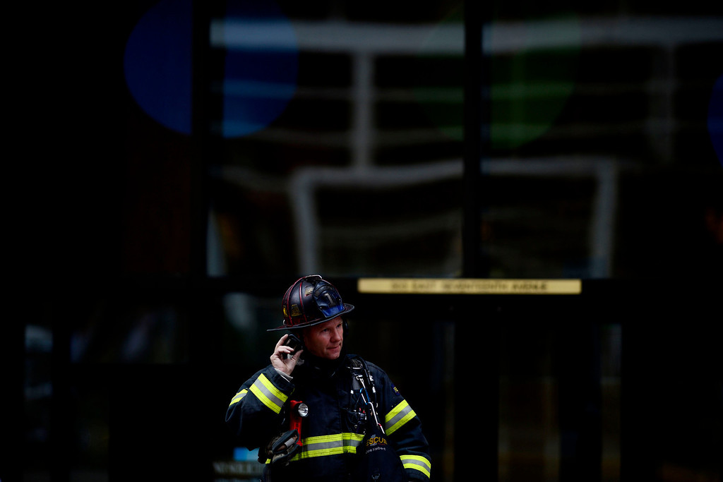 . A firefighter mans the front of 303 17th Avenue as fire crews work to put out a fire at a parking garage on 17th and Grant. A mechanical room began to burn and fire crews quickly put it out. As a precaution, the adjacent building was evacuated. (Photo by AAron Ontiveroz/The Denver Post)