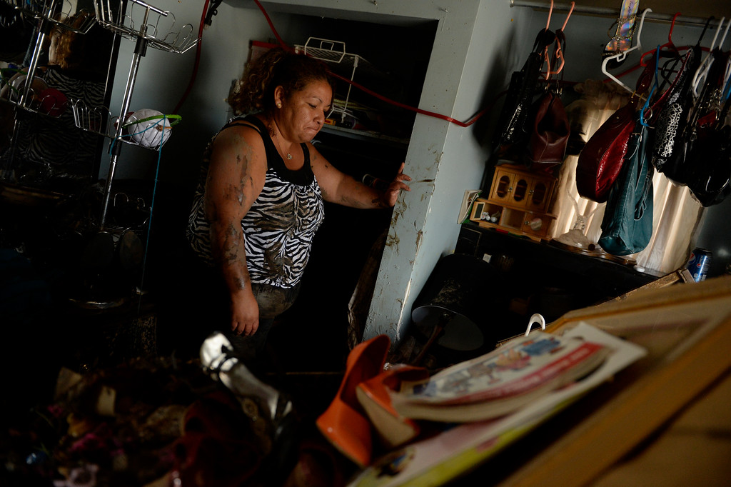 . EVANS, CO - SEPTEMBER 19: Araceli Romero was overwhelmed as she went through her home, in Evans, looking for belongings to save after the flood, September 19, 2013. Residents start to clean up after a massive flood hit the area. (Photo By RJ Sangosti/The Denver Post)