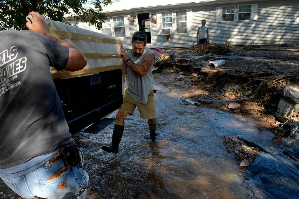 ". LYONS, CO. - SEPTEMBER 20: Scott Koester gets help from his nephew Kyron Brady, left, while carrying belongings from their home in Lyons, Colo. September 20, 2013. Koester expects that the home will be condemned after the recent flooding. He said, ""we\'ve been here 10 years now and it\'s all gone. I don\'t know how you\'d save this house.\"" Friday was the second day residents were allowed to return to their homes.  (Photo By Craig F. Walker / The Denver Post)"