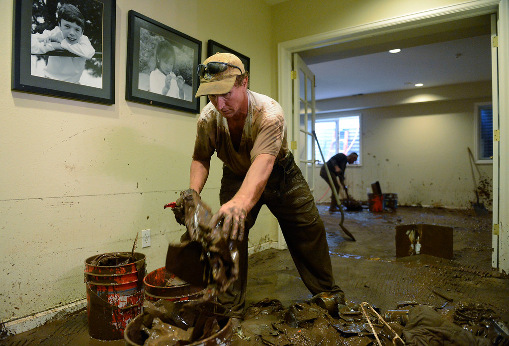 . BOULDER, CO - SEPTEMBER 13: Anatoliy Voythuov, a church volunteer, gathers muddy personal belongings at friend, Chris Vacek\'s house on Juniper Ave in Boulder Colorado on September 13, 2013. The Vacek\'s basement was a total loss. Everything was taken out and driven to the dump. (Photo By Andy Cross/The Denver Post)