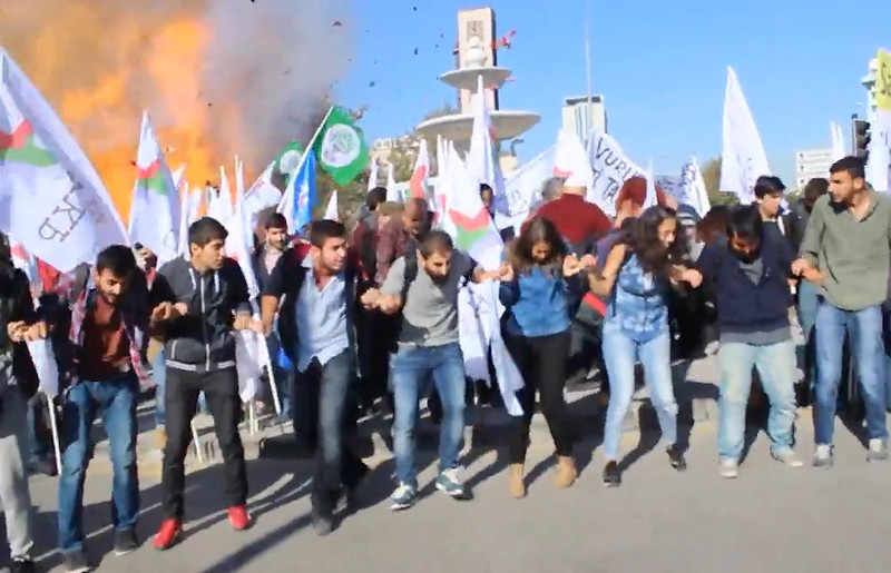 In this image made from video, participants in a peace rally react as an explosion happens behind them, in Ankara, Saturday, Oct. 10, 2015. Two explosions on Saturday targeted a peace rally by opposition supporters and Kurdish activists in Ankara, killing 86 people and wounding 186. The moment of one of the blast was caught on camera. Turkey's prime minister says the attacks likely were suicide bombings. Ahmet Davutoglu also declared a three-day official mourning period for the victims. (Dokuz8Haber via AP Video)