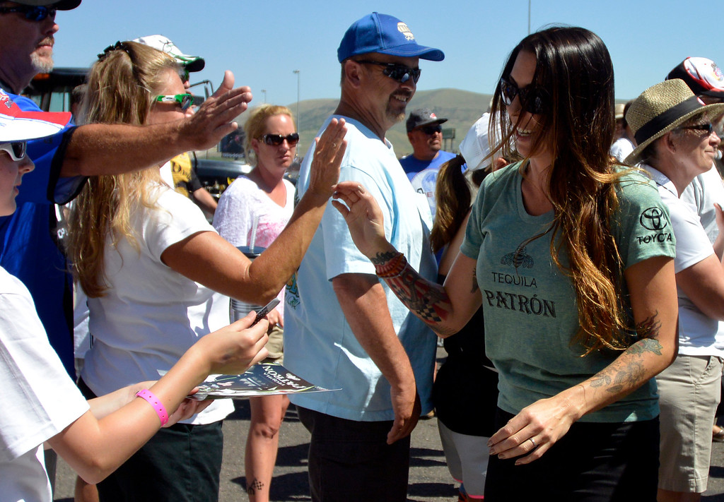 . Alexis DeJoria high fives fans during pre game festivities at the Mopar Mile-High NHRA Nationals July 21, 2013 at Bandimere speedway in Morrison. (Photo By John Leyba/The Denver Post)