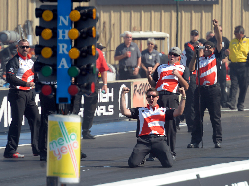 . Chris Abbott drops to his knees as Ethan Dooling and Mike Rodriguez celebrate behind him after Cruz Pedregon defeated Bob Tasca III in the Funn Car finals at the Mopar Mile-High NHRA Nationals July 21, 2013 at Bandimere speedway in Morrison. (Photo By John Leyba/The Denver Post)