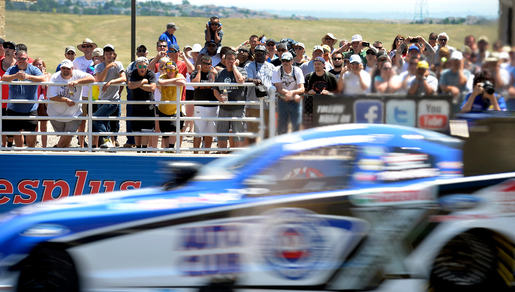 . Fans plug their ears as they watch the Robert Hight and Johnny Gray funny car race at the Mopar Mile-High NHRA Nationals July 21, 2013 at Bandimere speedway in Morrison. (Photo By John Leyba/The Denver Post)