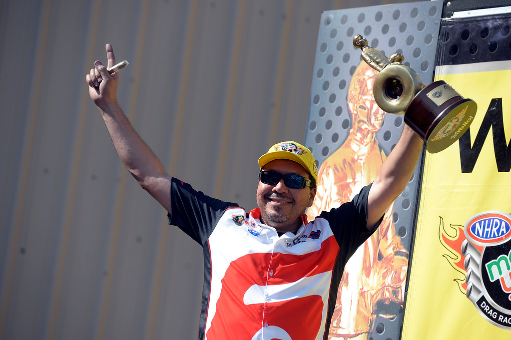 . Cruz Pedregon winner in the Funny Car finals hold up his trophy in the winner\'s circle at the Mopar Mile-High NHRA Nationals July 21, 2013 at Bandimere speedway in Morrison. (Photo By John Leyba/The Denver Post)