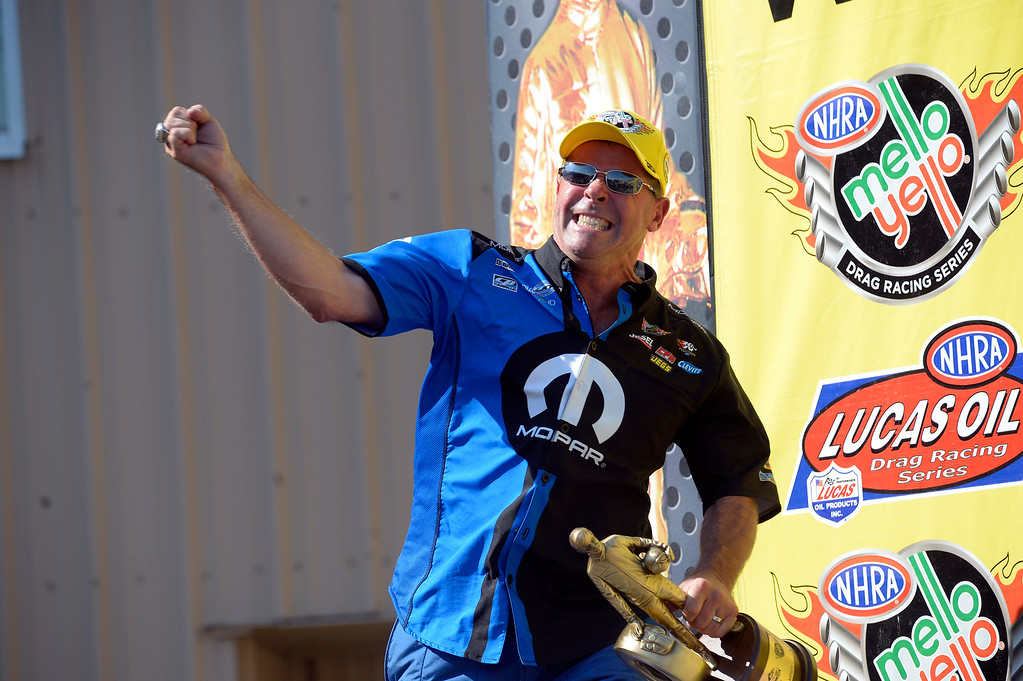 . Allen Johnson winner in the Pro Stock pumps his fist with his trophy in the winner\'s circle at the Mopar Mile-High NHRA Nationals July 21, 2013 at Bandimere speedway in Morrison. (Photo By John Leyba/The Denver Post)