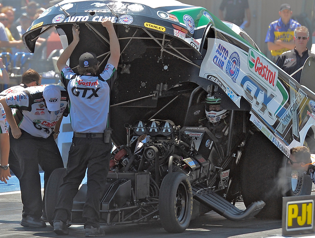 . John Force sits in his car after his burnout as he prepares for his race with Bob Tasca III int he first round of the Mopar Mile-High NHRA Nationals July 21, 2013 at Bandimere speedway in Morrison.  (Photo By John Leyba/The Denver Post)