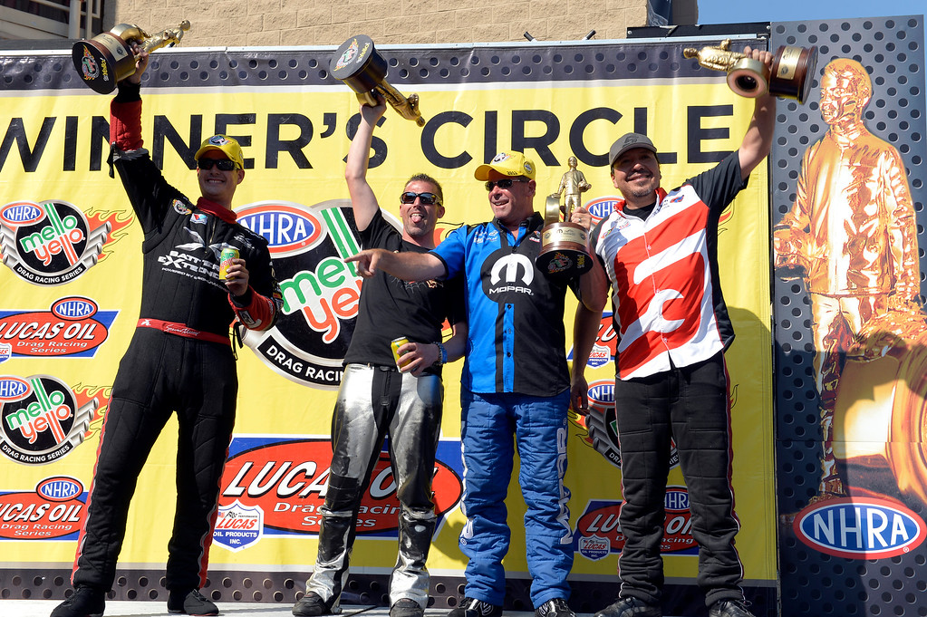. Left to right are Spencer Massey Top Fuel winner, Shawn Gann Pro Stock Motorcycle winner, Allen Johnson Pro Stock winner and Cruz Pedregon Funny Car winner hold up their trophy at the Mopar Mile-High NHRA Nationals July 21, 2013 at Bandimere speedway in Morrison. (Photo By John Leyba/The Denver Post)