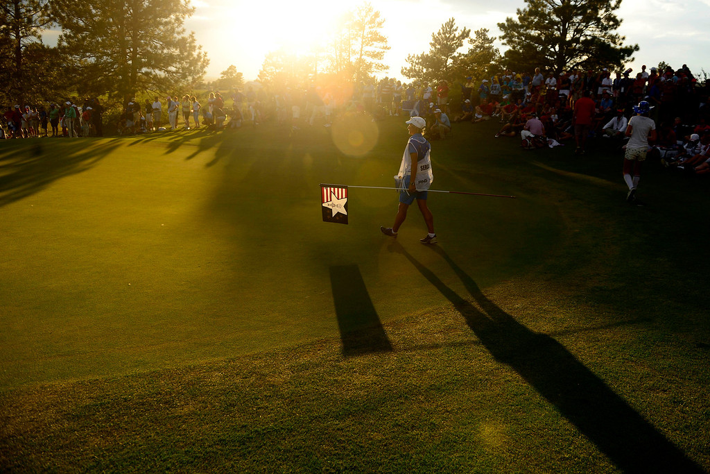 . PARKER, CO - AUGUST 18: Nadia Bortuzzi walks across the green with the pin in hand while serving as the caddy for Giulia Sergas during the final round of the Solheim Cup. WIth their win, the Europeans captured their first cup in the United States. (Photo by AAron Ontiveroz/The Denver Post)
