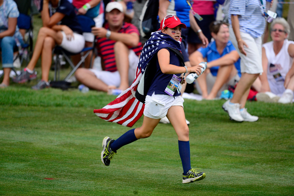 . A young fan runs across the course during the final round of the Solheim Cup. A win marks the first time the Europeans have won the competition in the United States. (Photo by AAron Ontiveroz/The Denver Post)
